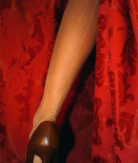 Bestrumpftes Bein vor rotem Vorhang